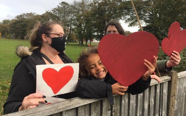 People showing hearts in support for refugees