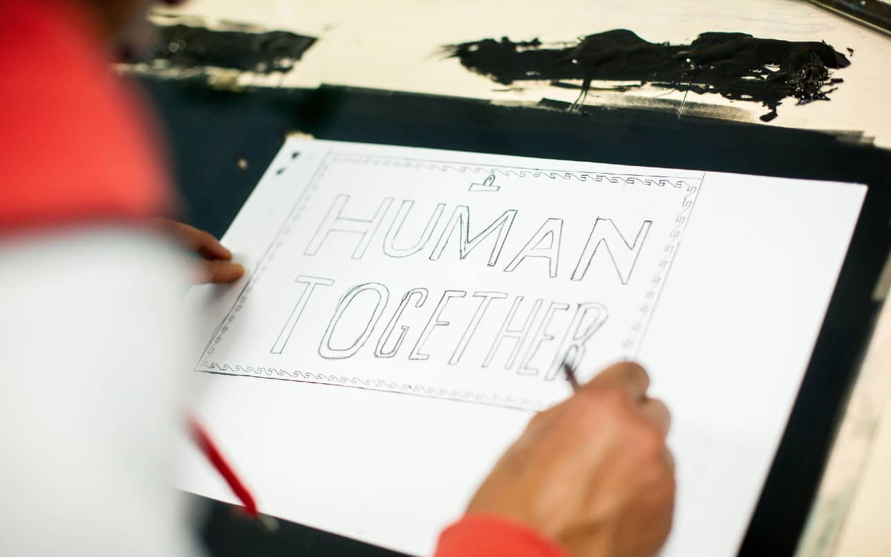 Person writing 'Human Together'